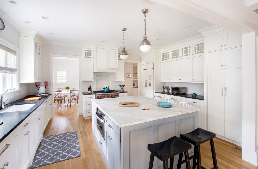 Large transitional u-shaped light wood floor kitchen photo in New York with an undermount sink, shaker cabinets, white cabinets, white backsplash, an island and paneled appliances