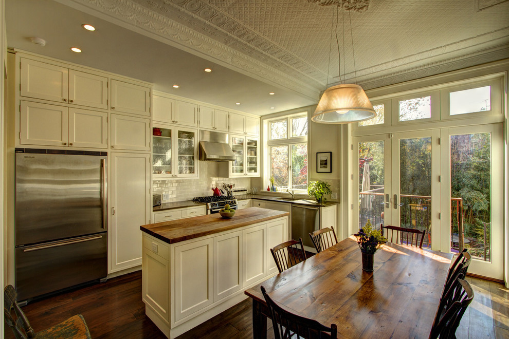 Eat-in kitchen - traditional l-shaped eat-in kitchen idea in New York with stainless steel appliances, wood countertops, an undermount sink, shaker cabinets, white cabinets, white backsplash and subway tile backsplash