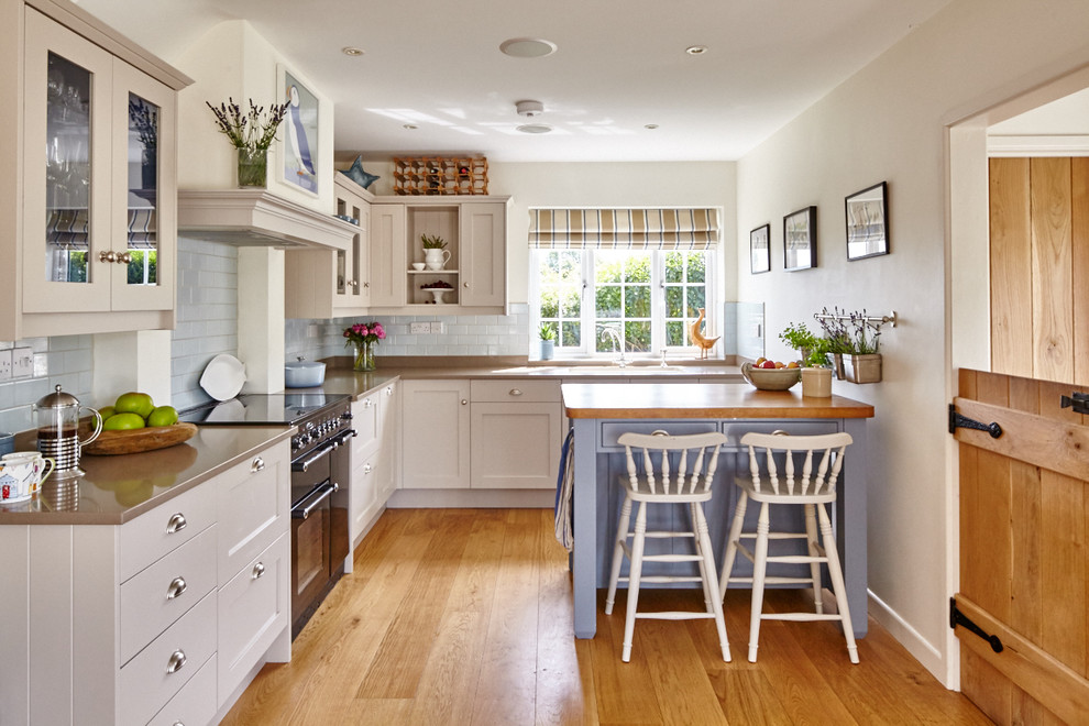 Inspiration for a country l-shaped medium tone wood floor kitchen remodel in Berkshire with shaker cabinets, white cabinets, blue backsplash, subway tile backsplash, black appliances and an island