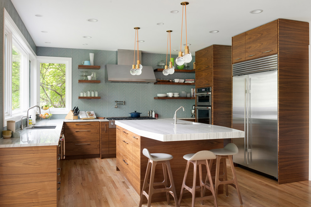 Kitchen - 1960s light wood floor kitchen idea in Minneapolis with a double-bowl sink, flat-panel cabinets, medium tone wood cabinets, blue backsplash, stainless steel appliances, an island and white countertops