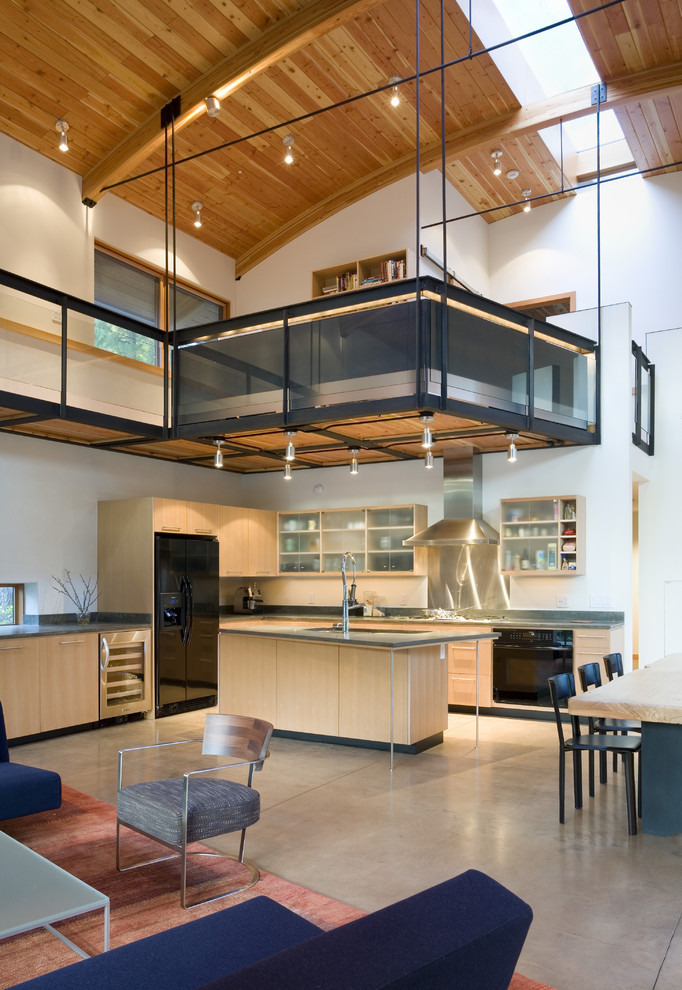 Example of a mid-sized trendy l-shaped concrete floor open concept kitchen design in Seattle with black appliances, glass-front cabinets, light wood cabinets, metallic backsplash, metal backsplash, solid surface countertops and an island