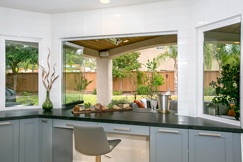 Example of a large transitional u-shaped medium tone wood floor and brown floor eat-in kitchen design in San Diego with gray cabinets, white backsplash, an undermount sink, shaker cabinets, quartzite countertops, subway tile backsplash, stainless steel appliances and an island