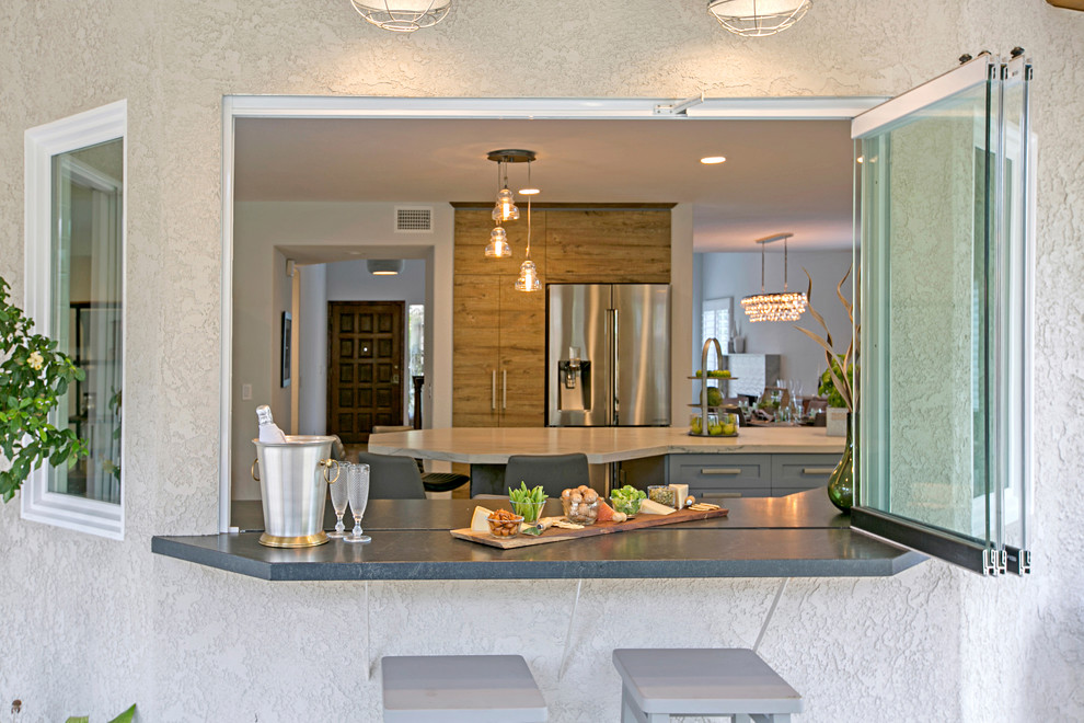 Example of a large transitional u-shaped medium tone wood floor and brown floor eat-in kitchen design in San Diego with an undermount sink, shaker cabinets, gray cabinets, quartzite countertops, white backsplash, subway tile backsplash, stainless steel appliances and an island