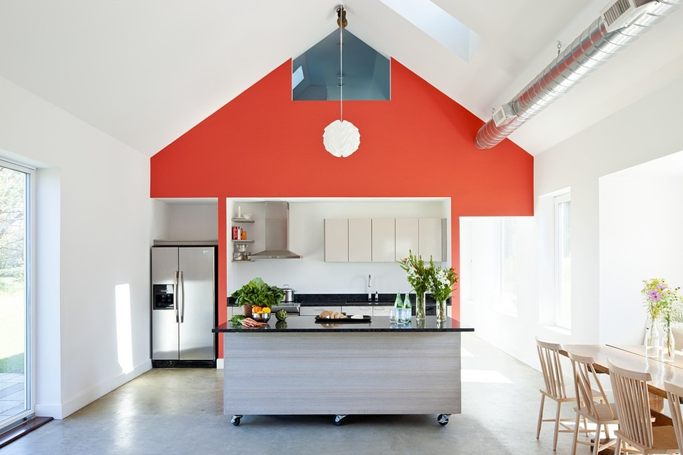 Cottage single-wall concrete floor and gray floor eat-in kitchen photo in Providence with an undermount sink, flat-panel cabinets, light wood cabinets, stainless steel appliances and an island