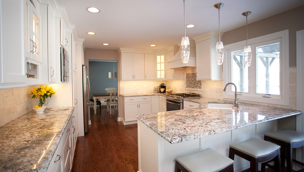 Example of a mid-sized transitional u-shaped dark wood floor eat-in kitchen design in Chicago with an undermount sink, shaker cabinets, white cabinets, granite countertops, beige backsplash, stone tile backsplash and stainless steel appliances
