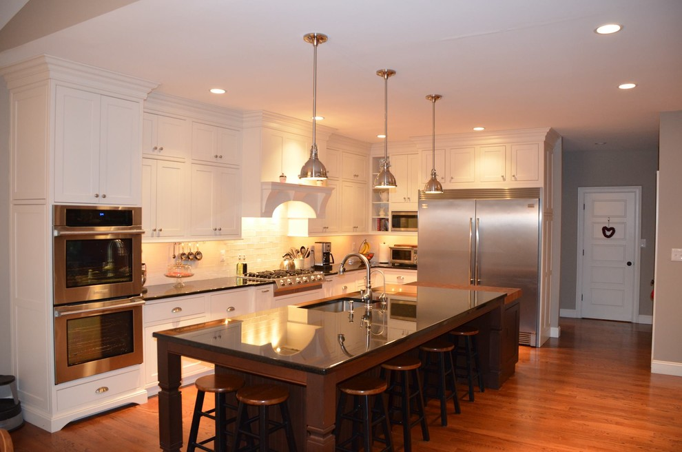 Eat-in kitchen - traditional l-shaped eat-in kitchen idea in Philadelphia with a single-bowl sink, beaded inset cabinets, white cabinets, granite countertops, beige backsplash, stone tile backsplash and stainless steel appliances