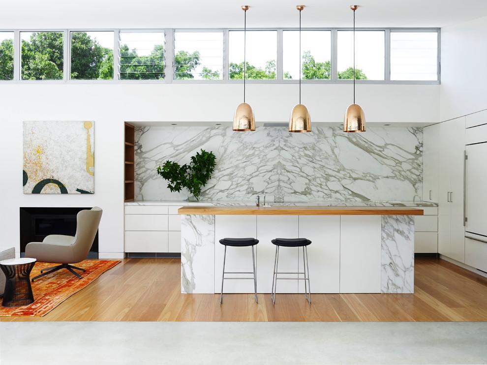 Ispirazione per un'ampia cucina ad ambiente unico design con ante lisce, ante bianche, top in marmo, un'isola, paraspruzzi bianco e elettrodomestici da incasso