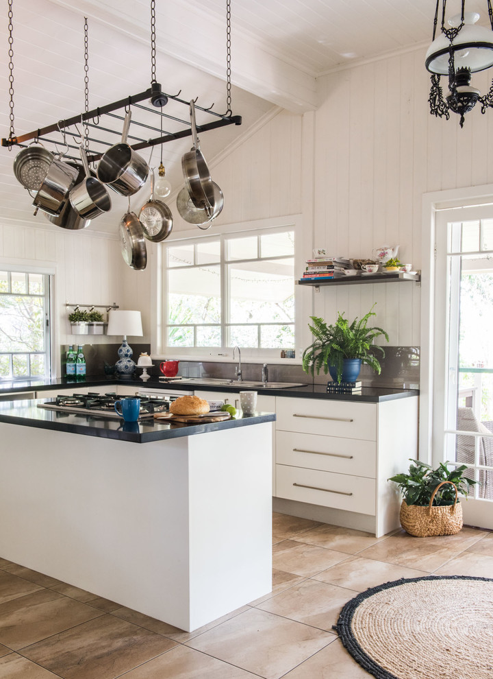 Example of a mid-sized farmhouse l-shaped porcelain tile open concept kitchen design in Brisbane with a double-bowl sink, flat-panel cabinets, white cabinets, granite countertops, glass sheet backsplash, stainless steel appliances, an island and gray backsplash