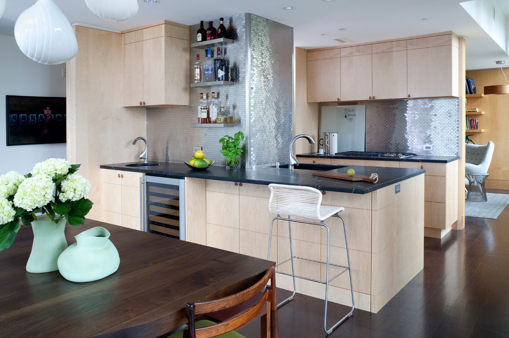 Inspiration for a mid-sized contemporary galley dark wood floor and brown floor eat-in kitchen remodel in DC Metro with flat-panel cabinets, light wood cabinets, metallic backsplash, metal backsplash, an undermount sink, stainless steel appliances and a peninsula