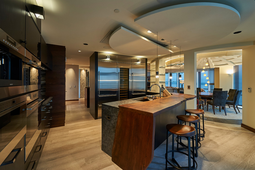 Example of a large trendy eat-in kitchen design in Other with dark wood cabinets, wood countertops and stainless steel appliances