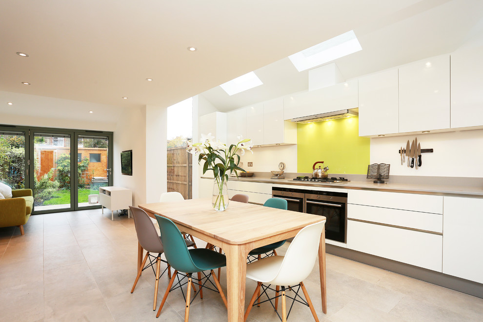 Example of a large trendy single-wall beige floor eat-in kitchen design in London with yellow backsplash, white cabinets, quartz countertops, glass sheet backsplash, stainless steel appliances and no island