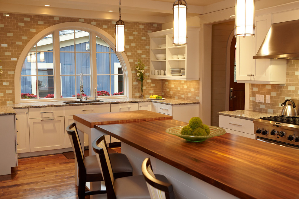 Example of a beach style kitchen design in Grand Rapids with wood countertops