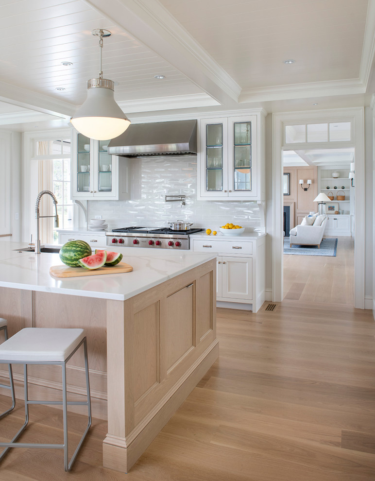 Kitchen - coastal medium tone wood floor, brown floor and shiplap ceiling kitchen idea in Providence with an undermount sink, recessed-panel cabinets, white cabinets, white backsplash, subway tile backsplash, stainless steel appliances, an island and white countertops