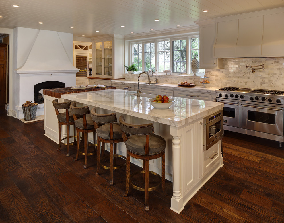 Kitchen - traditional dark wood floor kitchen idea in Cleveland with a farmhouse sink, shaker cabinets, white cabinets, white backsplash, stainless steel appliances and an island