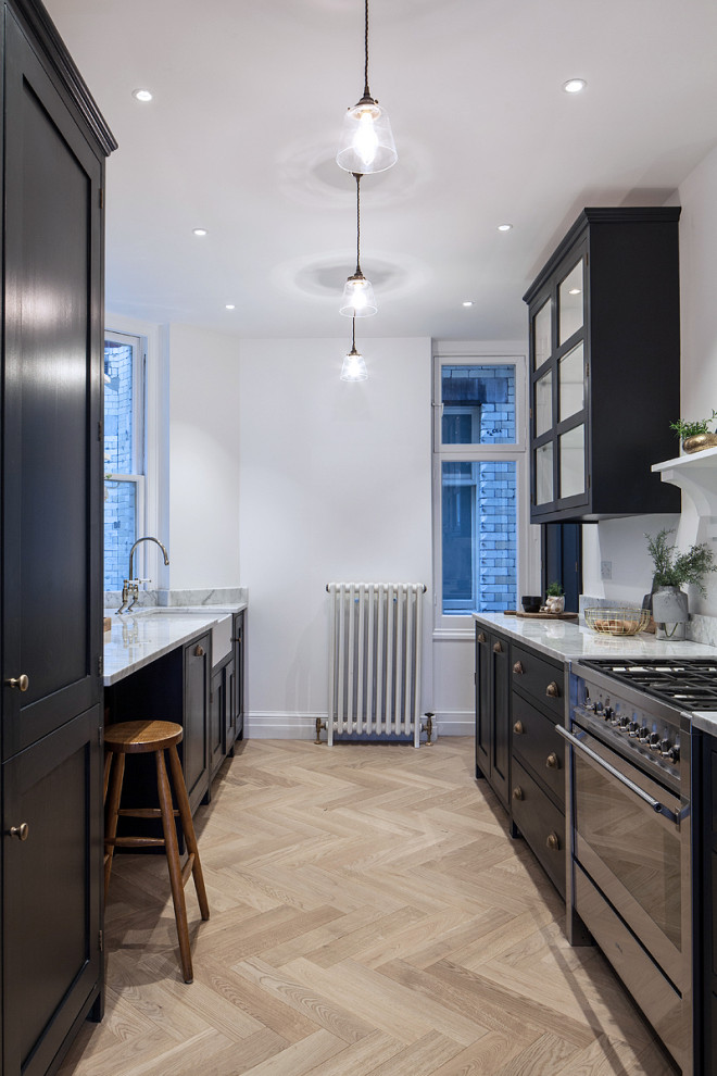 Inspiration for a medium sized rural galley kitchen in London with shaker cabinets, marble worktops, stainless steel appliances, a belfast sink, black cabinets, light hardwood flooring, no island, beige floors and white worktops.