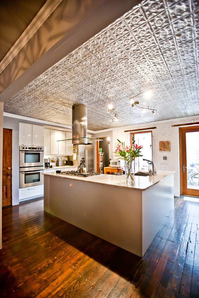 Mountain style kitchen photo in New York with marble countertops, stainless steel appliances, flat-panel cabinets and white cabinets