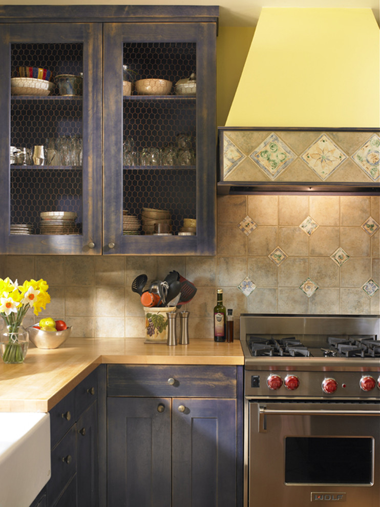 Inspiration for a shabby-chic style kitchen remodel in Seattle with stainless steel appliances, a farmhouse sink, wood countertops and distressed cabinets