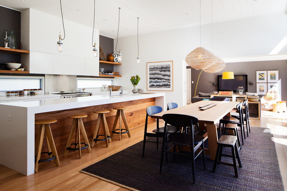 Eat-in kitchen - mid-sized contemporary galley medium tone wood floor eat-in kitchen idea in Sydney with flat-panel cabinets, white cabinets, metallic backsplash, stainless steel appliances and an island