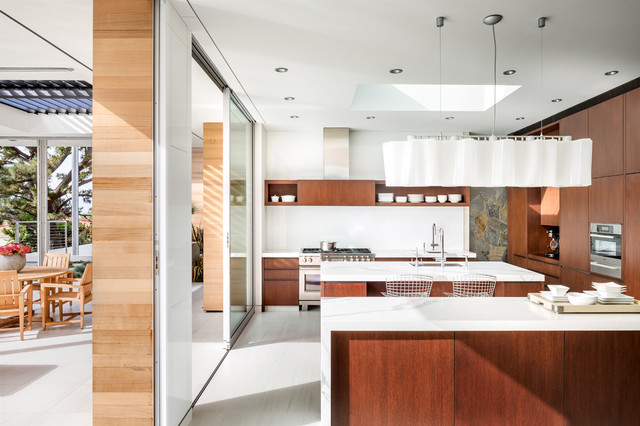 Eat-in kitchen - large modern galley ceramic floor and white floor eat-in kitchen idea in Los Angeles with an undermount sink, flat-panel cabinets, medium tone wood cabinets, marble countertops, white backsplash, glass tile backsplash, stainless steel appliances and two islands