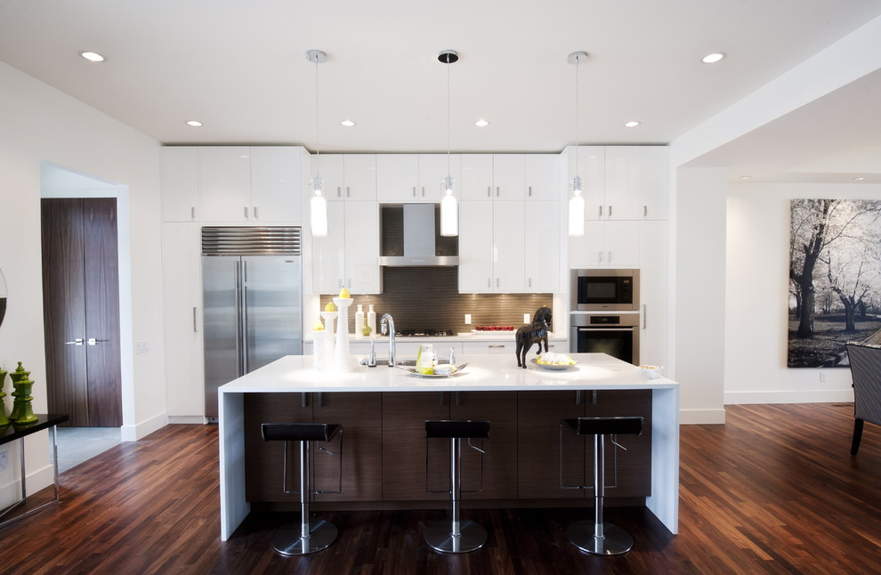 Inspiration for a contemporary galley eat-in kitchen remodel in Calgary with stainless steel appliances, flat-panel cabinets, white cabinets, quartz countertops and gray backsplash
