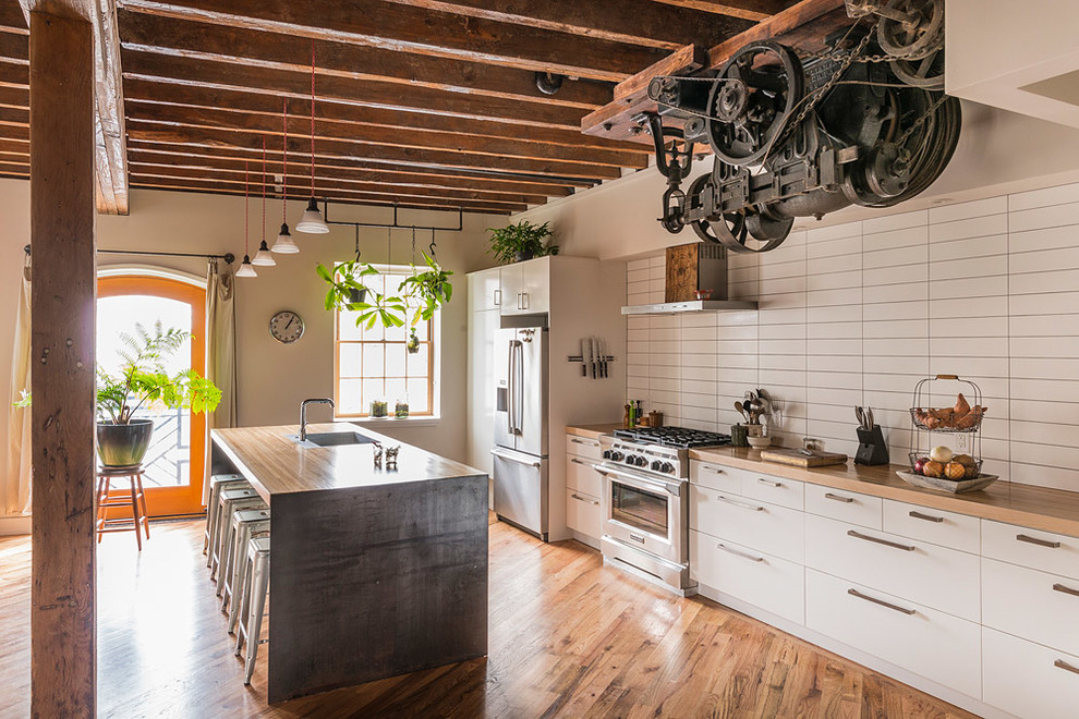Inspiration for an industrial galley medium tone wood floor kitchen remodel in Philadelphia with a single-bowl sink, flat-panel cabinets, white cabinets, wood countertops, white backsplash, stainless steel appliances and an island