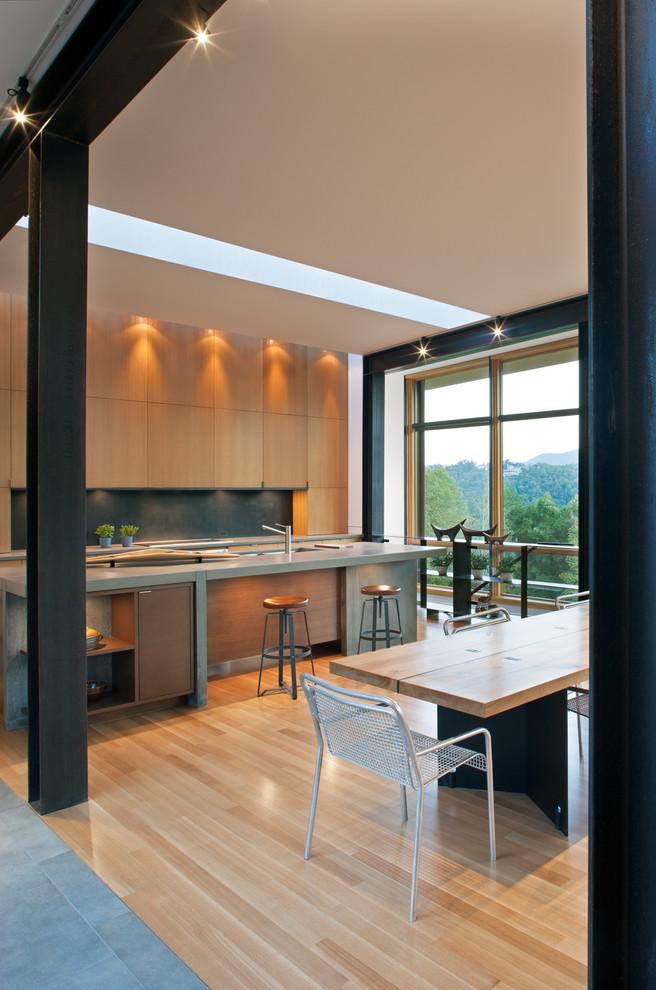 Ispirazione per una cucina minimalista con ante lisce, ante in legno chiaro, lavello integrato, paraspruzzi con piastrelle di metallo, parquet chiaro, pavimento beige, top in cemento, paraspruzzi nero e top grigio
