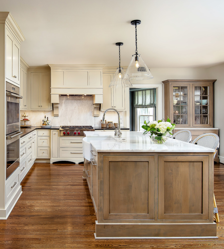 Example of a classic l-shaped medium tone wood floor kitchen design in New Orleans with a farmhouse sink, shaker cabinets, beige cabinets, beige backsplash, stainless steel appliances, an island and black countertops