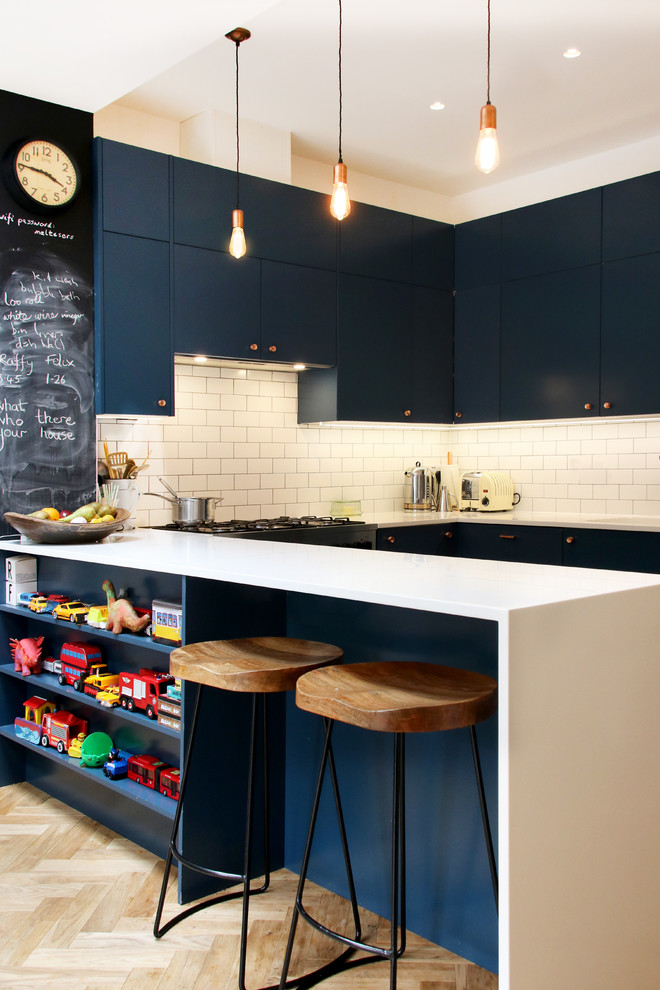 Trendy u-shaped light wood floor and beige floor kitchen photo in London with flat-panel cabinets, blue cabinets, white backsplash, subway tile backsplash, white countertops and a peninsula