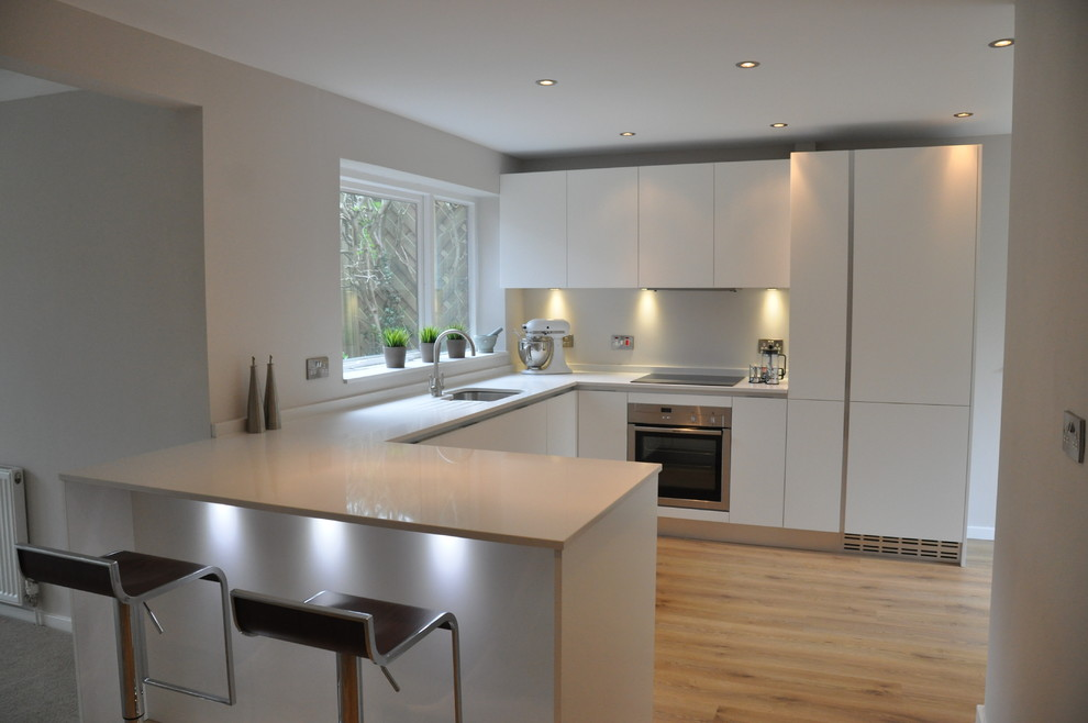 Inspiration for a small contemporary u-shaped kitchen/diner in Cheshire with a built-in sink, flat-panel cabinets, white cabinets, composite countertops, white splashback, glass sheet splashback, stainless steel appliances, medium hardwood flooring and a breakfast bar.