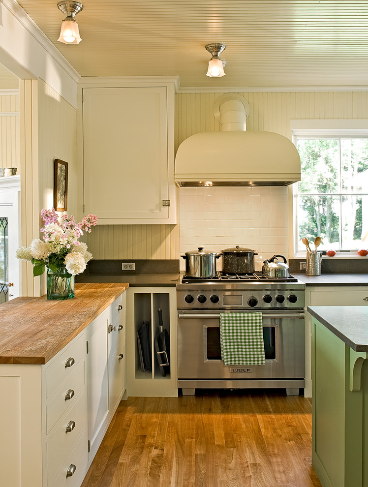 Example of a classic kitchen design in Portland Maine with wood countertops, shaker cabinets, white cabinets, white backsplash, subway tile backsplash and stainless steel appliances