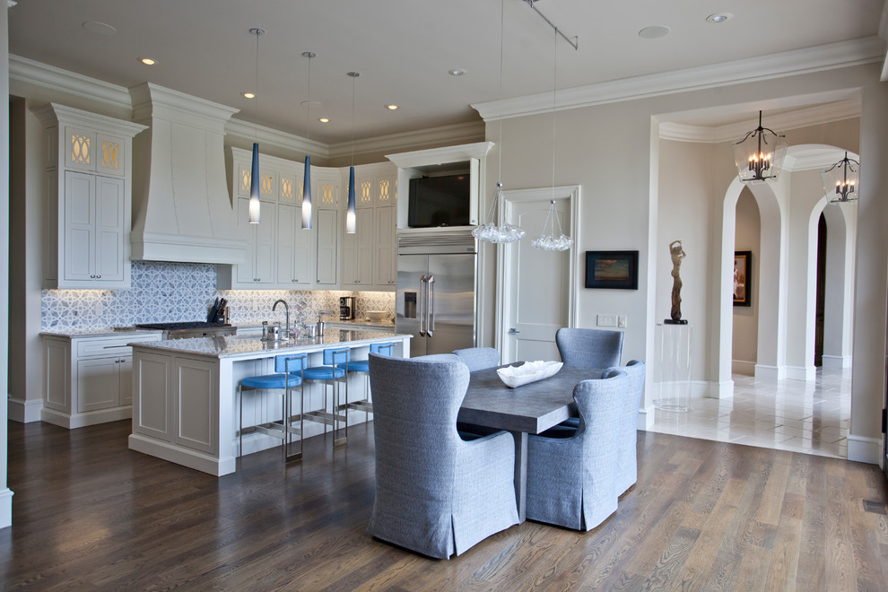 Eat-in kitchen - large mediterranean u-shaped medium tone wood floor and brown floor eat-in kitchen idea in Other with an undermount sink, recessed-panel cabinets, white cabinets, granite countertops, blue backsplash, ceramic backsplash, stainless steel appliances, an island and white countertops