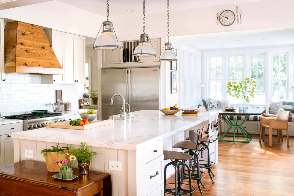 Elegant medium tone wood floor and beige floor eat-in kitchen photo in Raleigh with shaker cabinets, gray cabinets, white backsplash, subway tile backsplash, stainless steel appliances, an island and marble countertops
