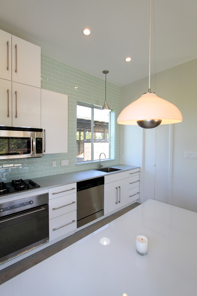 Minimalist single-wall eat-in kitchen photo in Austin with a single-bowl sink, flat-panel cabinets, white cabinets, green backsplash, glass tile backsplash and stainless steel appliances