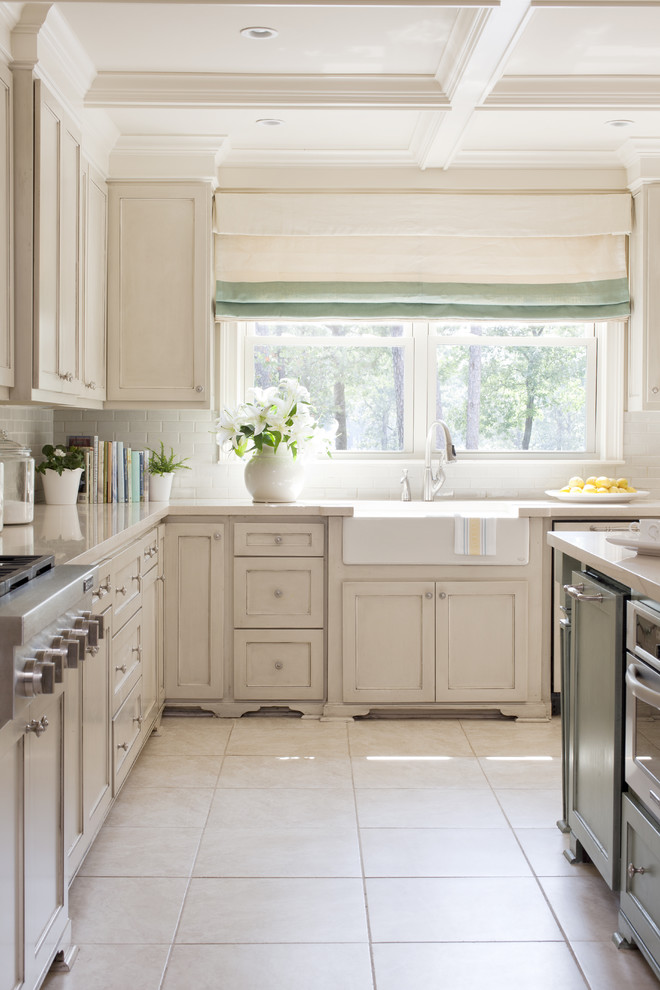 Mid-sized transitional u-shaped eat-in kitchen photo in Little Rock with a farmhouse sink, recessed-panel cabinets, beige cabinets, quartz countertops, white backsplash, subway tile backsplash, paneled appliances and an island
