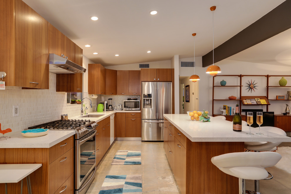 Mid-sized mid-century modern ceramic tile eat-in kitchen photo in Los Angeles with a double-bowl sink, flat-panel cabinets, light wood cabinets, soapstone countertops, white backsplash, mosaic tile backsplash, stainless steel appliances and an island