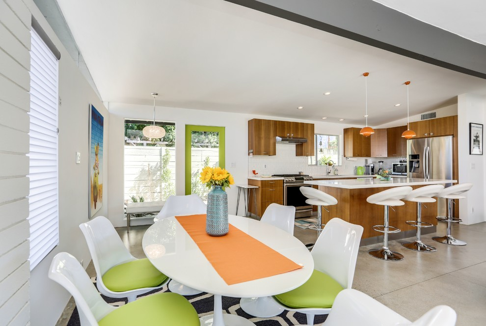Inspiration for a mid-sized 1960s ceramic tile eat-in kitchen remodel in Los Angeles with a double-bowl sink, flat-panel cabinets, light wood cabinets, soapstone countertops, white backsplash, mosaic tile backsplash, stainless steel appliances and an island