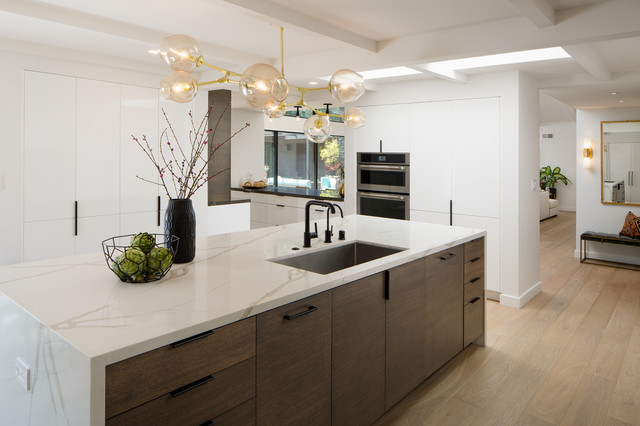 Large minimalist u-shaped light wood floor and brown floor eat-in kitchen photo in San Diego with an undermount sink, flat-panel cabinets, white cabinets, laminate countertops, black backsplash, marble backsplash, paneled appliances, an island and white countertops