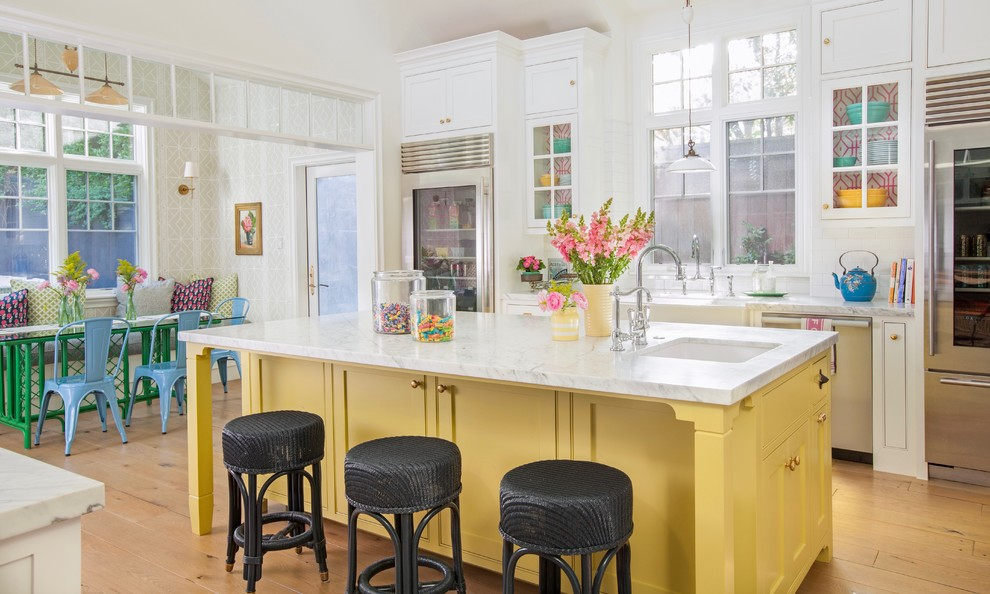 Inspiration for a huge cottage galley light wood floor and beige floor kitchen remodel in Los Angeles with a farmhouse sink, shaker cabinets, yellow cabinets, marble countertops, white backsplash, ceramic backsplash, stainless steel appliances and an island