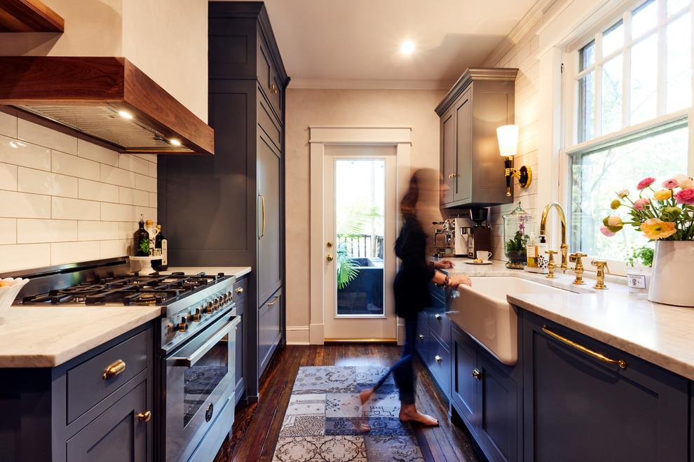 Elegant galley dark wood floor enclosed kitchen photo in Atlanta with a farmhouse sink, shaker cabinets, blue cabinets, white backsplash, subway tile backsplash, stainless steel appliances and no island