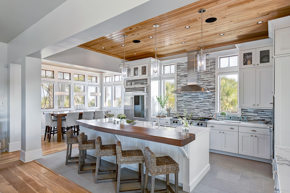Example of a beach style galley kitchen design in Jacksonville with matchstick tile backsplash, marble countertops, shaker cabinets, white cabinets, stainless steel appliances and multicolored backsplash