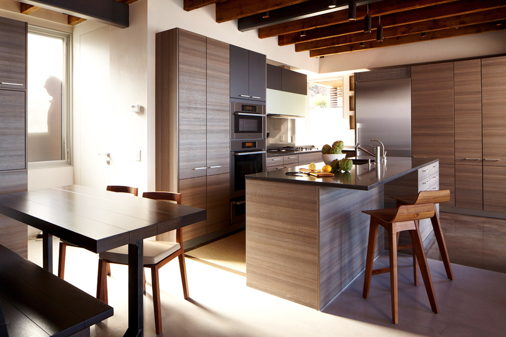 Mid-sized minimalist l-shaped concrete floor eat-in kitchen photo in New York with stainless steel appliances, flat-panel cabinets, dark wood cabinets, quartz countertops, an undermount sink and an island