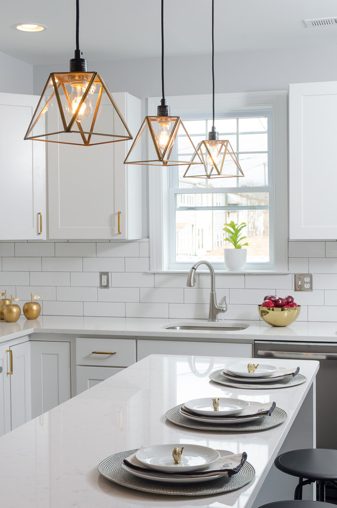 Example of a transitional kitchen design in DC Metro with an undermount sink, shaker cabinets, white cabinets, white backsplash, subway tile backsplash, stainless steel appliances and an island