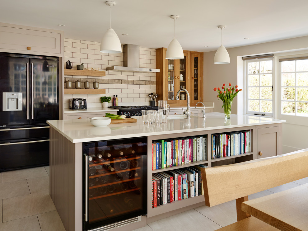Example of a classic kitchen design in London with an island and beige cabinets