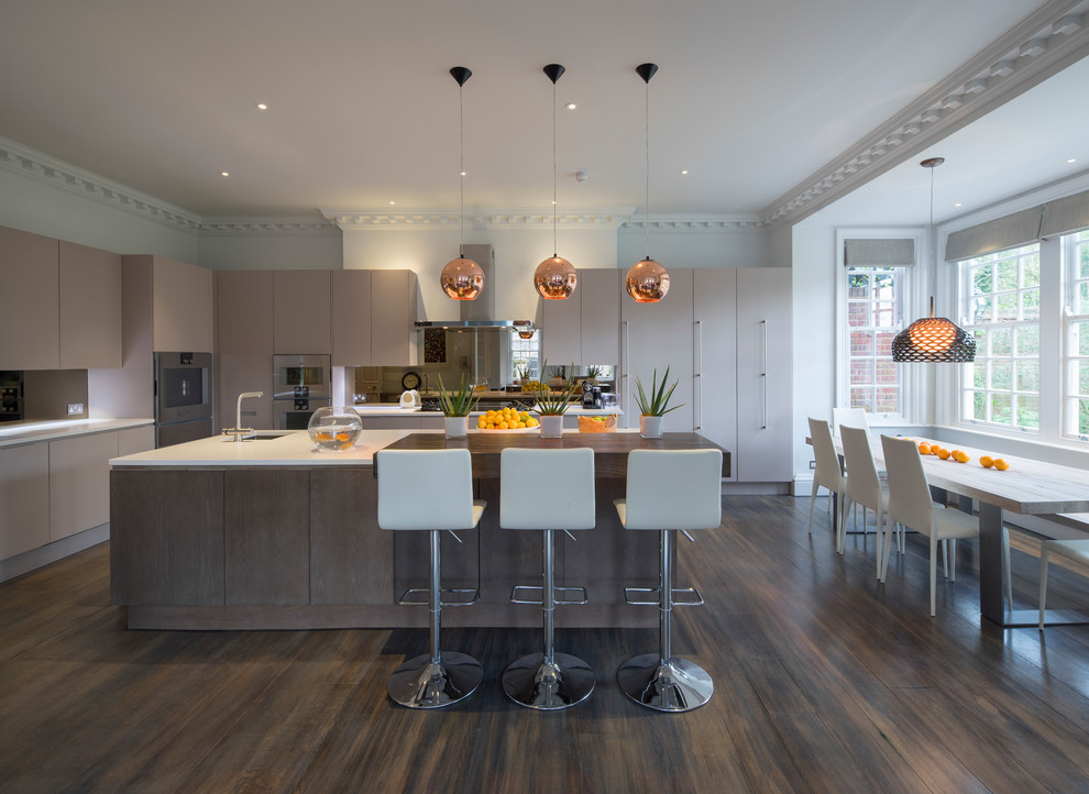 Eat-in kitchen - contemporary l-shaped dark wood floor eat-in kitchen idea in London with an undermount sink, flat-panel cabinets, beige cabinets, paneled appliances and an island