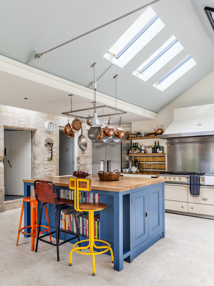 Inspiration for an eclectic kitchen in London with recessed-panel cabinets, blue cabinets, wood worktops, stainless steel appliances and an island.