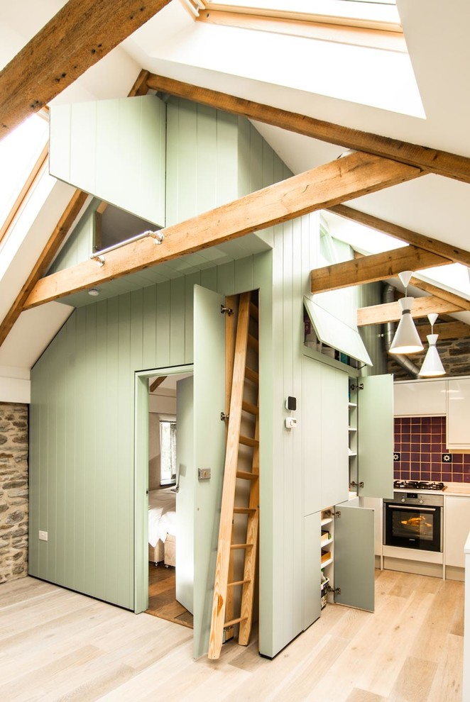Eat-in kitchen - small farmhouse l-shaped light wood floor eat-in kitchen idea in London with flat-panel cabinets, green cabinets, red backsplash and ceramic backsplash