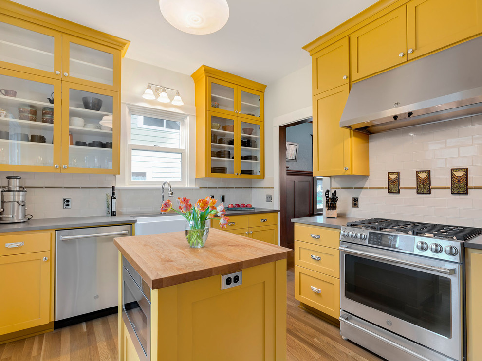 Inspiration for a large craftsman light wood floor enclosed kitchen remodel in Portland with a farmhouse sink, shaker cabinets, yellow cabinets, quartz countertops, subway tile backsplash, stainless steel appliances, an island, gray countertops and white backsplash