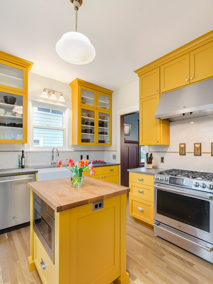 Inspiration for a large craftsman u-shaped light wood floor enclosed kitchen remodel in Portland with a farmhouse sink, shaker cabinets, yellow cabinets, quartz countertops, multicolored backsplash, subway tile backsplash, stainless steel appliances, an island and gray countertops