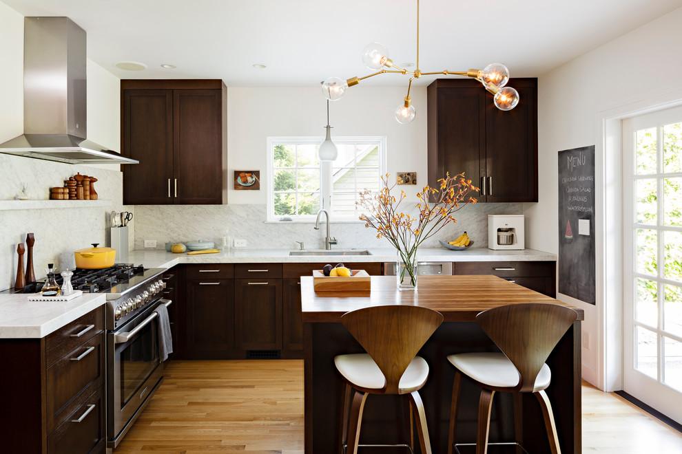 Kitchen - mid-sized contemporary l-shaped medium tone wood floor kitchen idea in Portland with wood countertops, stainless steel appliances, shaker cabinets, dark wood cabinets, white backsplash, stone slab backsplash and an undermount sink