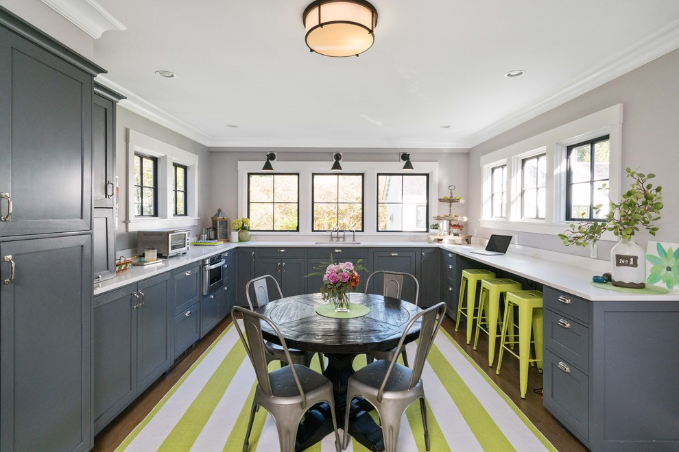 Transitional u-shaped medium tone wood floor and brown floor kitchen photo in Boston with shaker cabinets, gray cabinets, stainless steel appliances and no island